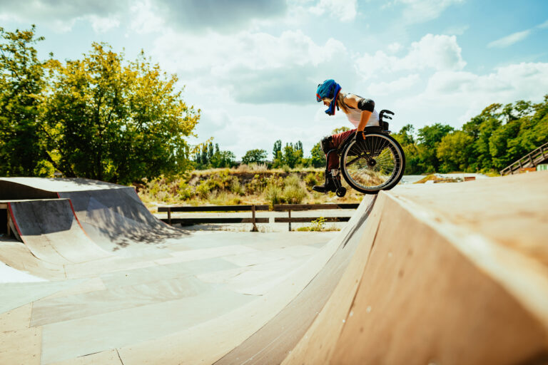 Disabled millennial woman in wheelchair rolls down the hills in skate park